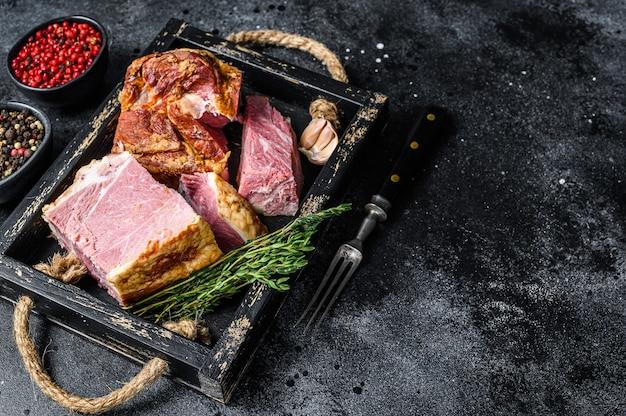 Boczek wędzony plasterki plastry wieprzowiny mięso w drewnianej tacy. czarne tło. widok z góry. skopiuj miejsce.