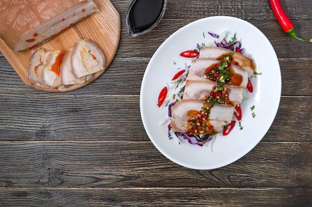 Boczek wieprzowy z surówką z kapusty w białej misce na drewnianym tle. chiński kuzyn. widok z góry.