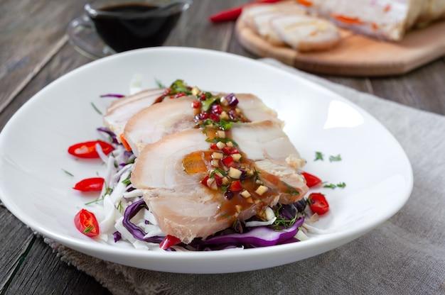 Boczek wieprzowy z surówką z kapusty w białej misce na drewnianym tle. chiński kuzyn.