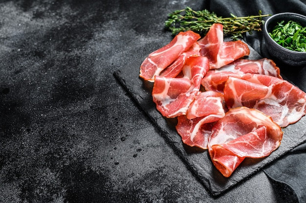 Boczek włoski rolowany pancetta piacentina. wieprzowina. czarne tło. widok z góry. skopiuj miejsce.