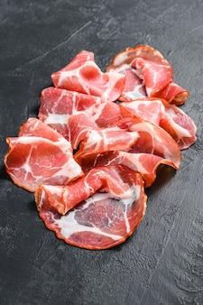 Boczek włoski rolowany pancetta piacentina. wieprzowina. czarne tło. widok z góry.