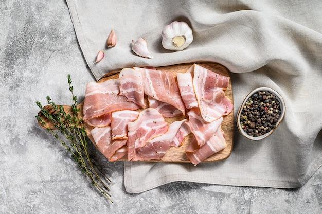 Boczek z pieprzem i tymiankiem na desce do krojenia. ekologiczne surowe mięso wieprzowe