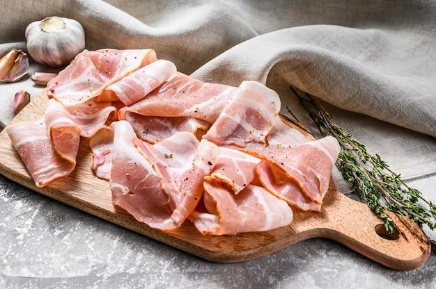 Boczek z pieprzem i tymiankiem na desce do krojenia. organiczne surowe mięso wieprzowe.