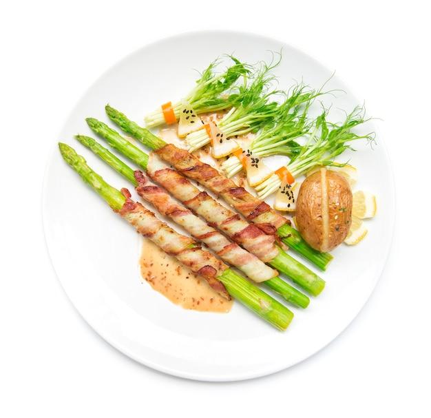 Boczek zawijany szparagi grillowane z sosem sasemi i kiełkami grochu roll w chili sałatka czarny sasemi udekoruj piec ziemniaki cheddar widok z góry izolowany