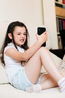 Boczna widok dziewczyna robi gderliwej twarzy dla fotografii