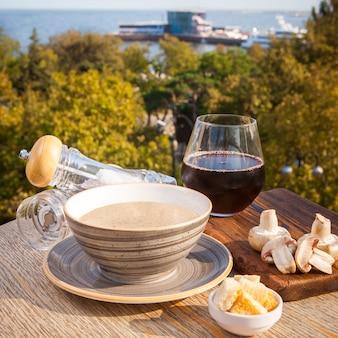 Boczna zupa grzybowa z pieczarkami, wino na lekkim drewnianym stole w nadmorskiej restauracji