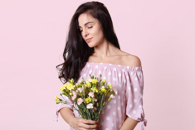 Boczne ujęcie zadowolonej, zadowolonej europejki o ciemnych włosach, trzyma bukiet kwiatów, zamyka oczy z radości