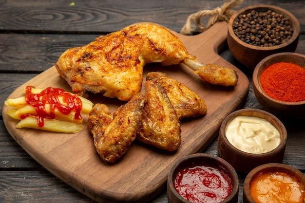 Boczne zbliżenie miski z kurczakiem i przyprawami z kolorowymi sosami i przyprawami oraz udko z kurczaka i skrzydełka oraz frytki na desce do krojenia