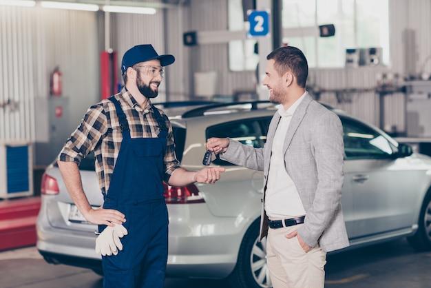 Boczne zdjęcie profilowe biznesmen przedstawiający kluczyki do samochodu technikowi w mundurze