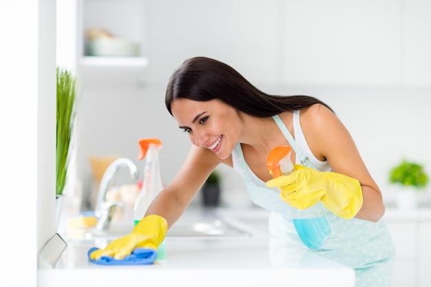 Boczne zdjęcie profilowe pozytywnej pokojówki w fartuchu w kropki sprzątanie domu za pomocą żółtych gumowych rękawiczek niebieska szmata na stole do mycia blat w kuchni
