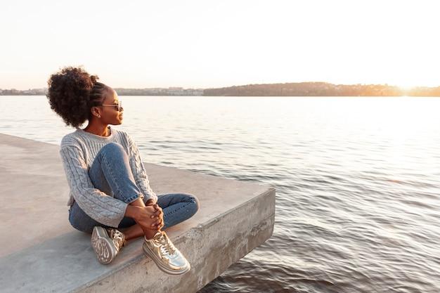 Bocznego widoku afrykańska kobieta pozuje outside