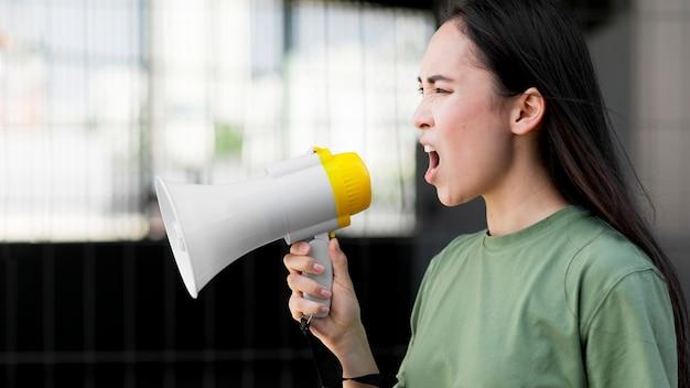 Bocznego widoku azjatykcia kobieta krzyczy w megafonie