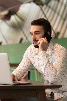 Bocznego widoku biznesowy mężczyzna opowiada przy telefonem