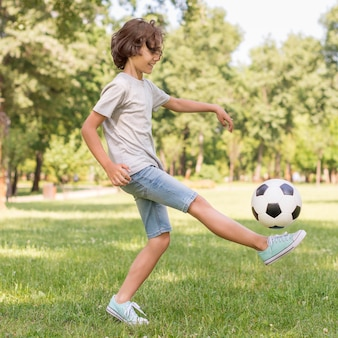 Bocznego widoku chłopiec bawić się z futbolową piłką