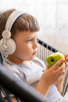 Bocznego widoku chłopiec je jabłka z hełmofonami