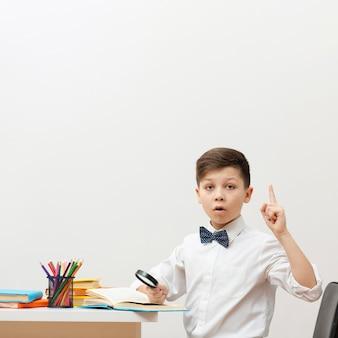 Bocznego widoku chłopiec przy biurka czytaniem