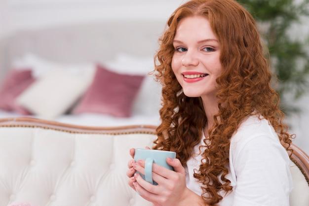 Bocznego widoku czerwona włosiana kobieta pije herbaty