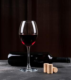 Bocznego widoku czerwone wino na czarnym vertical