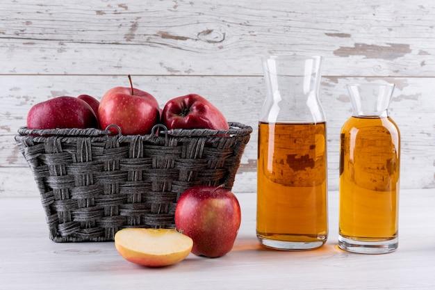 Bocznego widoku czerwoni jabłka w koszu z sokiem na białym drewnianym stole