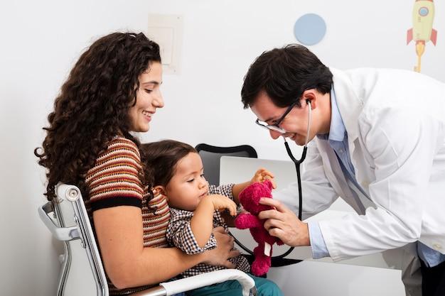 Bocznego widoku doktorska sprawdza chłopiec