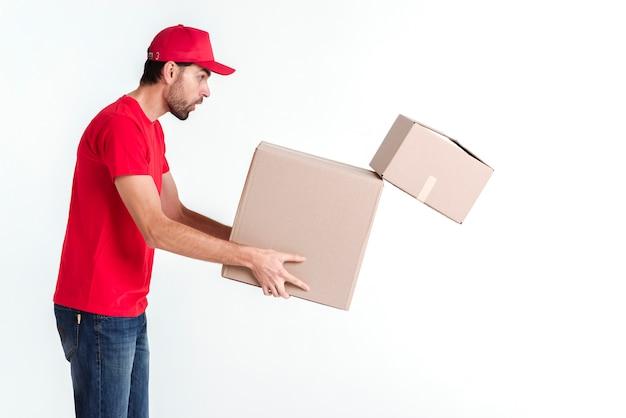 Bocznego widoku doręczeniowy chłopiec trzyma pakuneczek wysyła pudełka i opuszcza jeden