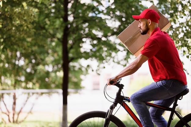 Bocznego widoku doręczeniowy mężczyzna niesie pakuneczek na rowerze
