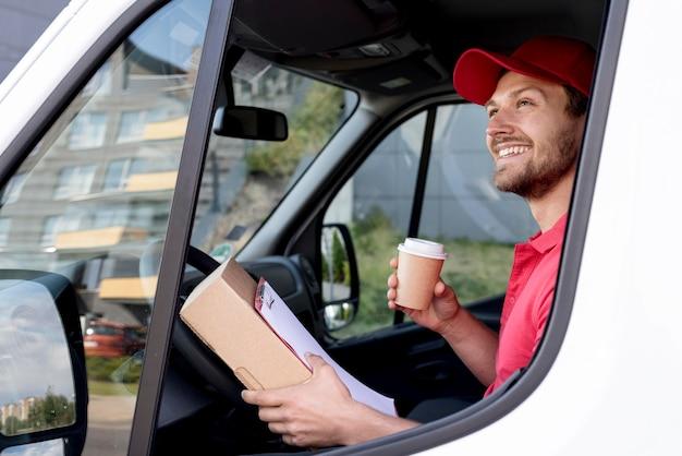 Bocznego widoku doręczeniowy mężczyzna z kawą w samochodzie