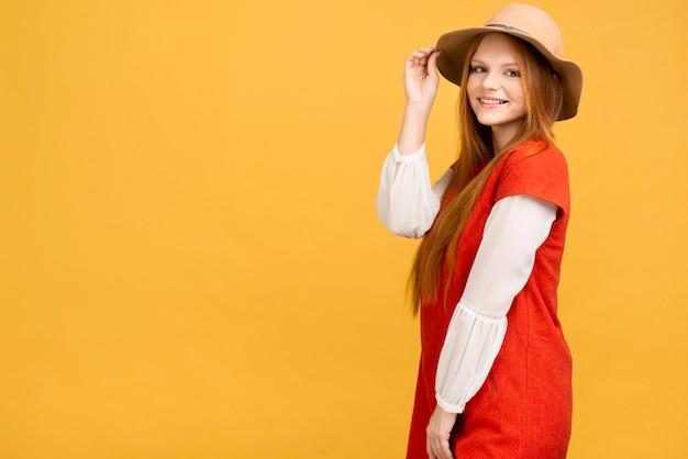 Bocznego widoku dziewczyna pozuje z kapeluszem
