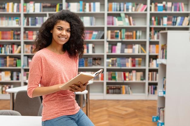 Bocznego widoku dziewczyna przy bibliotecznym czytaniem