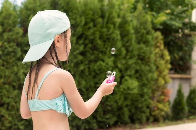 Bocznego widoku dziewczyna robi mydlanym bąblom