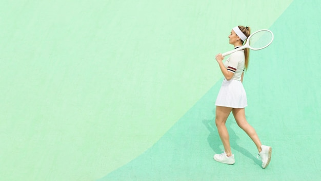 Bocznego widoku dziewczyna z tenisowym kantem na tenisowym polu