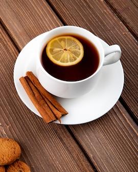 Bocznego widoku filiżanka herbata z plasterkiem cytryna i cynamon z ciastkami na drewnianym tle