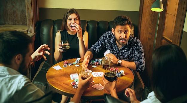 Bocznego widoku fotografia przyjaciele siedzi przy drewnianym stołem. przyjaciele zabawy podczas gry planszowej.