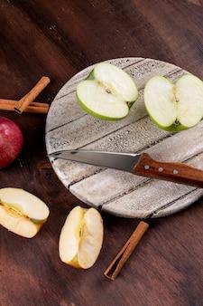Bocznego widoku jabłka pokrajać z nożem na białej deski vertical