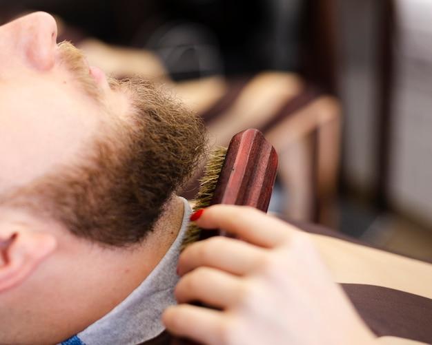 Bocznego widoku klient ma jego brody przygotowywającego zakończenie