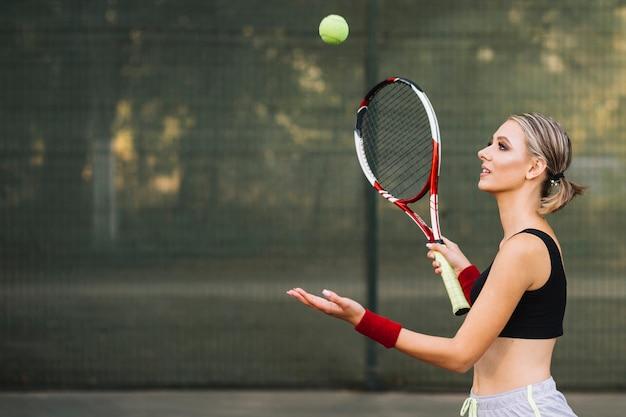 Bocznego widoku kobieta bawić się tenisa na polu