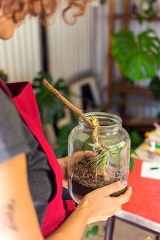 Bocznego widoku kobieta bierze opiekę rośliny w słoju