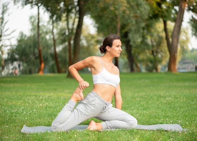 Bocznego widoku kobieta ćwiczy na joga macie