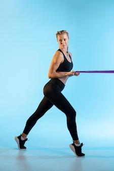 Bocznego widoku kobieta ćwiczy z elastycznym zespołem