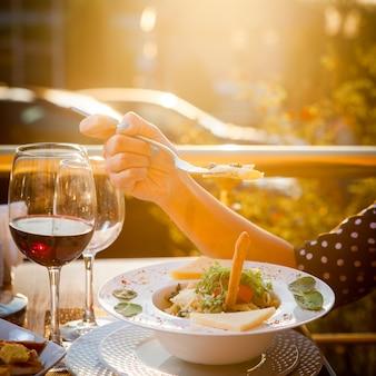 Bocznego widoku kobieta je sałatki z szkłem wino na stole z drzewami i światło słoneczne przecieka na tle
