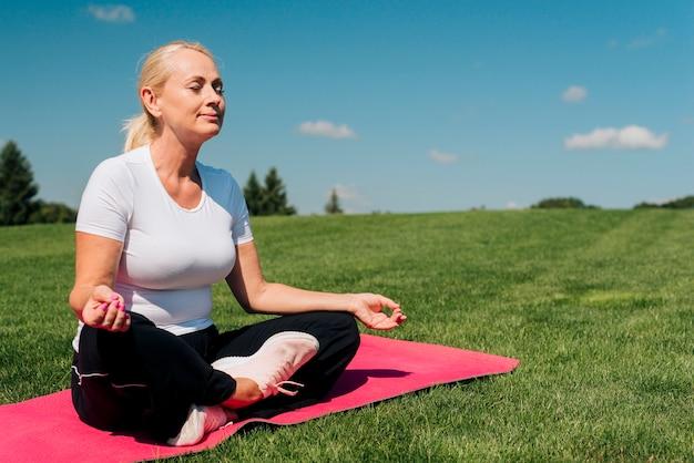 Bocznego widoku kobieta medytuje w naturze