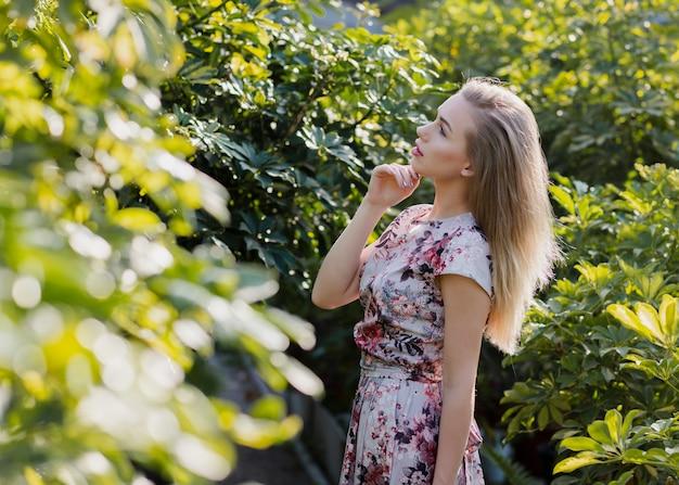 Bocznego widoku kobieta patrzeje roślina liście