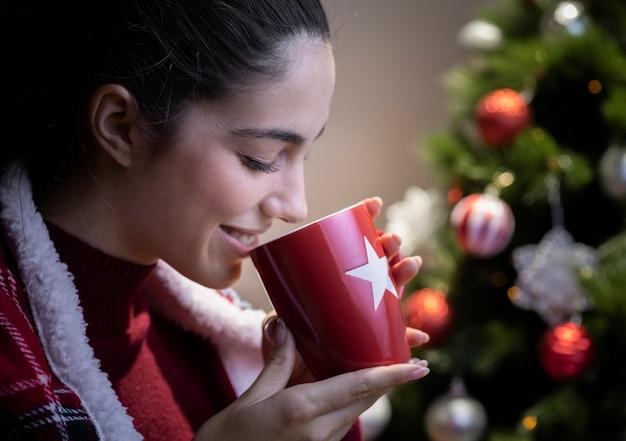 Bocznego widoku kobieta pije herbaty na bożych narodzeniach