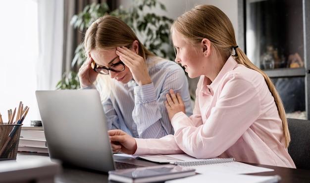 Bocznego widoku kobieta pomaga młodej dziewczynie z pracą domową
