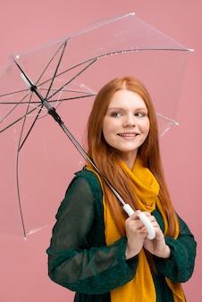 Bocznego widoku kobieta pozuje z parasolem