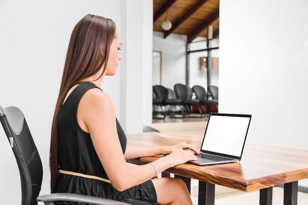 Bocznego widoku kobieta pracuje na jej laptopie