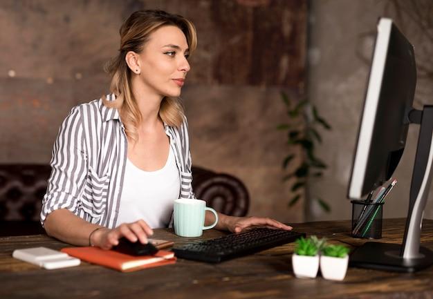 Bocznego widoku kobieta pracuje na komputerze