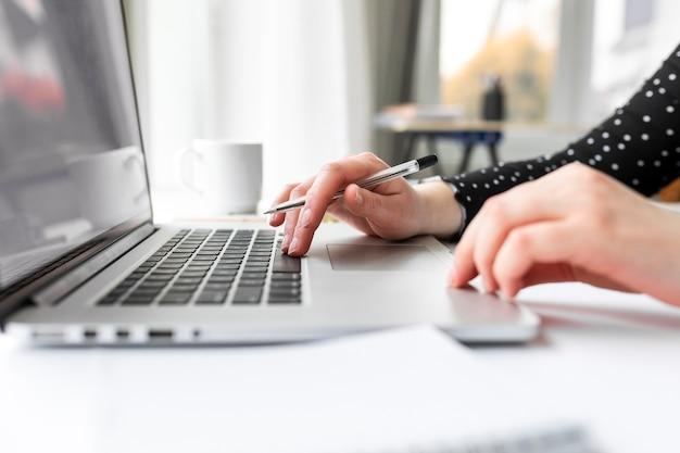 Bocznego widoku kobieta pracuje na laptopie