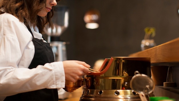 Bocznego widoku kobieta pracuje w sklep z kawą
