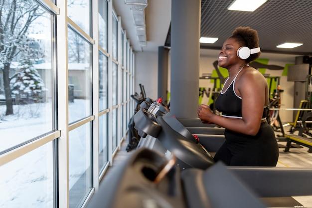 Bocznego widoku kobieta przy gym bieg na karuzeli